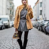 With a Grey Dress, a Furry Coat, and Black Over-the-Knee Boots