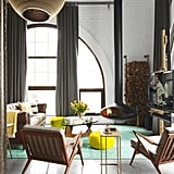 """In the living room, Anthony softened the industrial impact of the tall ceilings and concrete floor by installing a hanging Fire Orb fireplace and piling on honey-toned woods and a mix of textures. He finished the look with a leather Timothy Oulton sofa, floor-to-ceiling curtains made from Sunbrella fabric, tweedy midcentury-modern armchairs from Dot & Bo, and an easel-shaped TV stand from Restoration Hardware. The real standout pieces, though, are the bright floor accents, like the overdyed rug from Wayfair. """"Most people put color on their walls, but here I wanted the energy to come from the ground,"""" said Anthony."""
