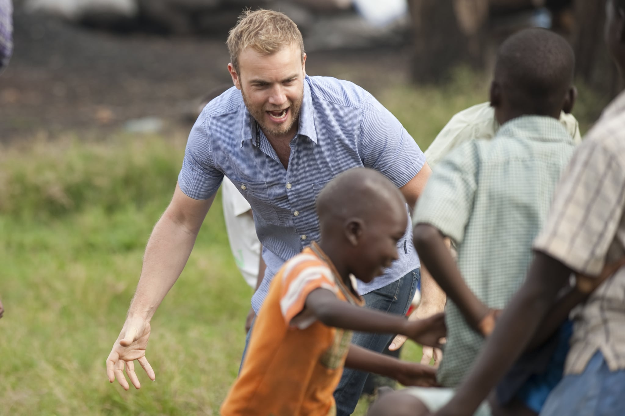 HOIMA, UGANDA - NOVEMBER 29: Gary Barlow plays with the local children before heading to the Bulimya net distribution area on November 29, 2009 in Hoima, Uganda. Five of the nine celebrity Kilimanjaro climbers, Gary Barlow, Fearne Cotton, Ben Shepherd, Chris Moyles and Kimberley Walsh, saw all their hard work climbing the mighty Mount Kilimanjaro pay off as they witnessed for themselves how some of the money raised is being spent to help to fight malaria, Africa's biggest killer. The team are revisiting Africa to see how the money raised over Red Nose Day is being spent, as well as helping to hand out malaria nets. You can see how the team got on by watching BBC One 6.30pm Sunday 27th December.  (Photo by Des Willie/Comic Relief via Getty Images)