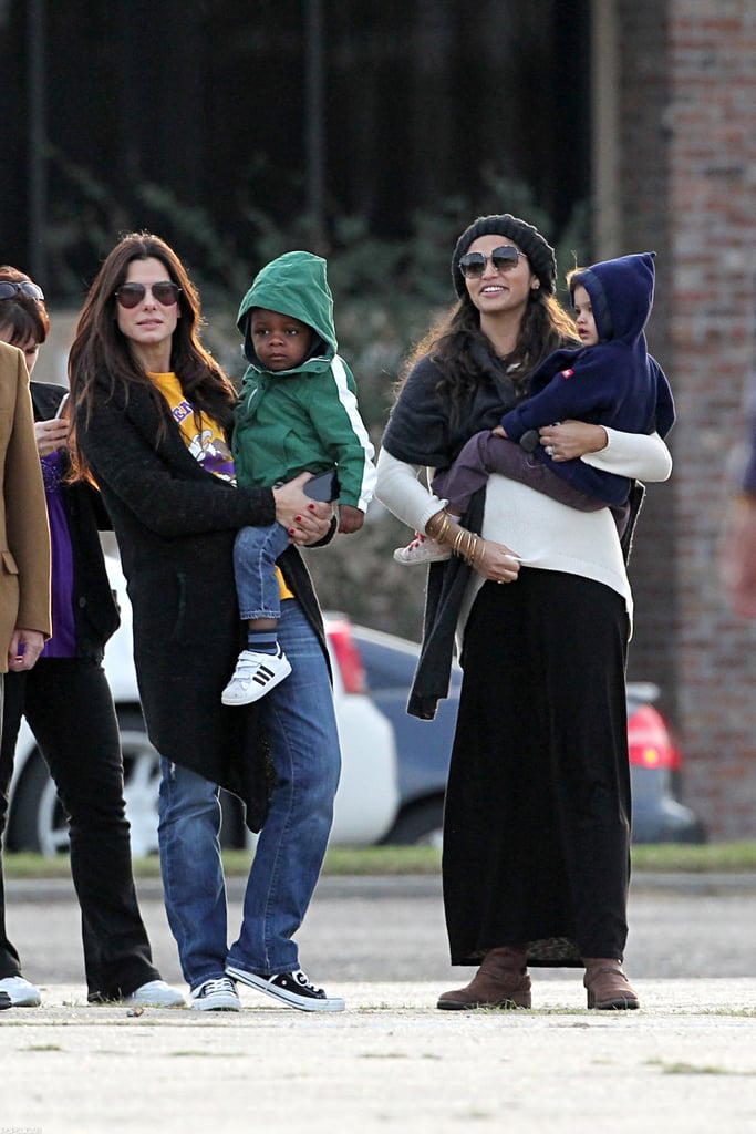 Sandra Bullock and Camila Alves took their kids to watch the Warren Easton Charter High School marching band perform in New Orleans yesterday. Sandra donated money to help restore the school after it was damaged by Hurricane Katrina in 2005. She's since continued her charitable contributions, helping them open a health clinic in 2010 and giving the charter organization money for scholarships this year.  Sandra had her son, Louis, in her arms while a pregnant Camila juggled Levi and Vida with the help of a friend during the fun outing. Camila and her family are in Louisiana while Matthew McConaughey films The Dallas Buyer's Club. Matthew lost over 30 pounds for the role and has been showing off his shocking weight loss on set in recent days. It looks like Sandra and Camila have become pals through Matthew, since Sandra and Matthew have remained friends after dating in the '90s. They have something more in common, since Sandra, Matthew, and their families both have homes in Austin, TX.