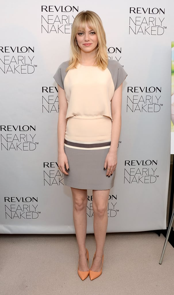 Emma Stone paired her gray and ivory dress with orange pumps.