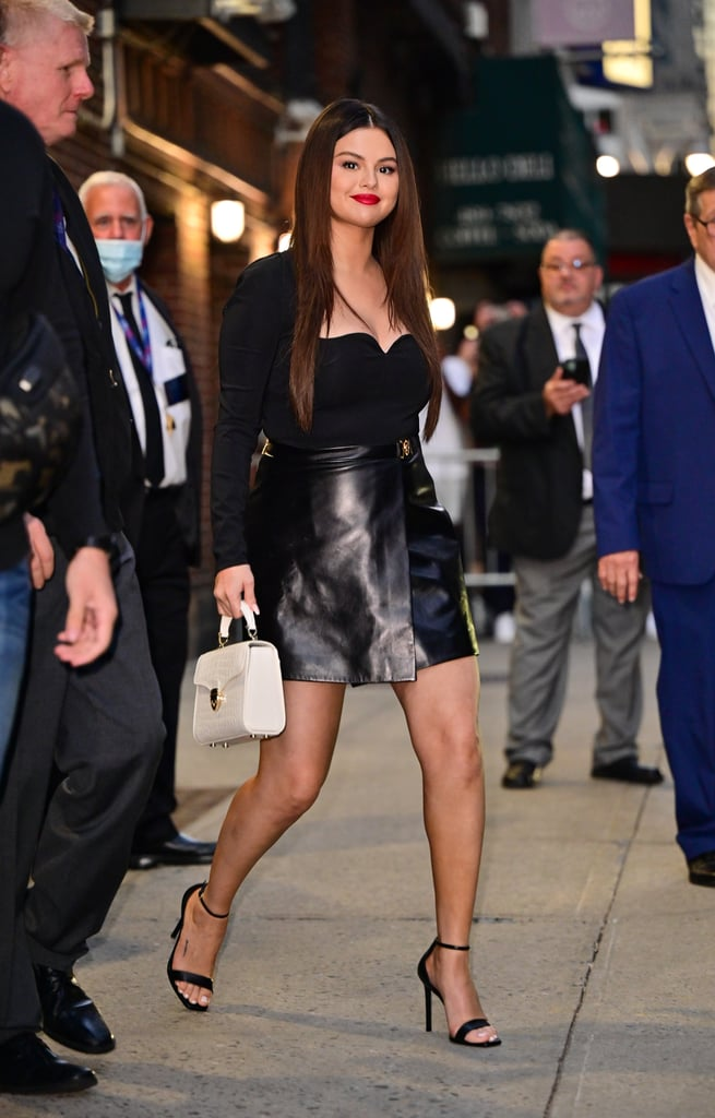 It wasn't the falling temperatures, pumpkin spice lattes, or Halloween costumes that finally had me registering summer was coming to an end — it was the all-black outfit Selena Gomez wore for a recent appearance on The Late Show With Stephen Colbert to promote her new show Only Murders in the Building with costars Steve Martin and Martin Short. Transitional and chic yet subtly sexy, the look consisted of a jersey bodysuit with a sweetheart neckline under a buttery leather miniskirt, courtesy of Versace. After months of reaching for bright colors and bold prints, Selena's simple ensemble reminds me just how sleek head-to-toe black can be. Oh, how I've missed my dark hues and leather pieces. The actress effortlessly paired her fall outfit with black heeled sandals to match and a white snakeskin purse. Ahead, get a 360 view of Selena's sophisticated look.      Related:                                                                                                           Selena Gomez's Only Murders in the Building Looks Make a Very Good (and Easy!) Halloween Costume