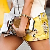 A shining box clutch and spiky jewellery complement golden shorts.