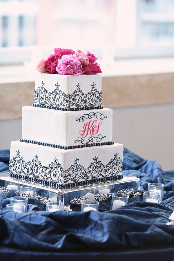 "The whimsical black trim, the pink peonies, the personalized initials — so much about this cake screams ""romantic."""