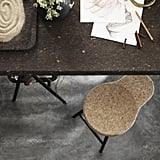 Cork is used on many surfaces in the collection. A thin layer covers the top of this dining table ($349) and stool ($59).