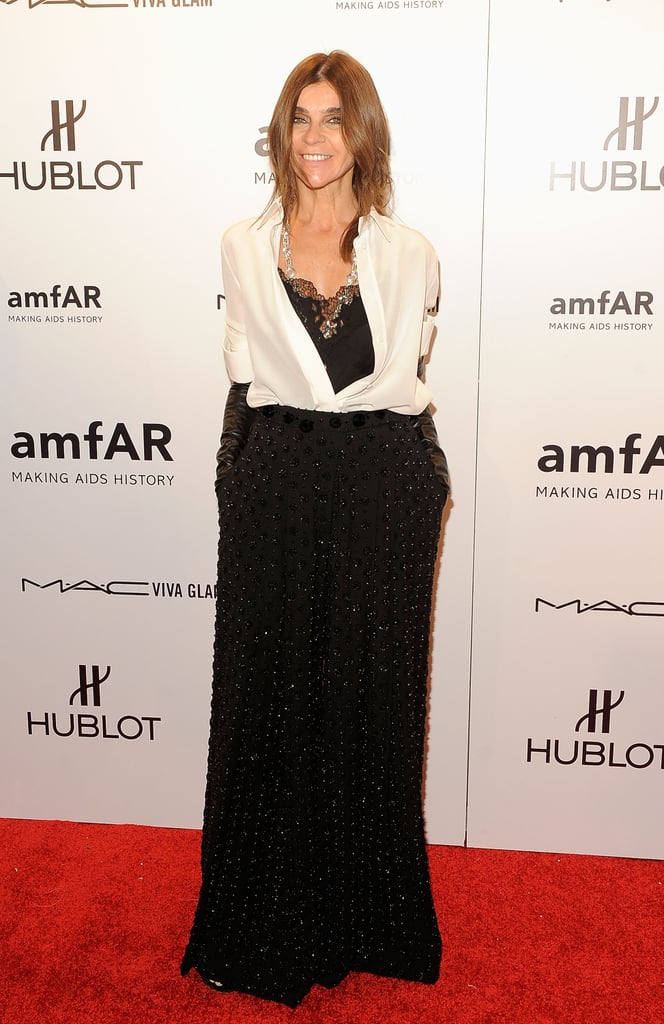Carine Roitfeld tucked a white silk blouse into a long black skirt. She added black leather gloves to the mix, which gave the illusion of a slicker, more suited-up look.