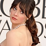 Zooey Deschanel rarely appears on a red carpet without her signature bangs, and this curly midheight ponytail at the Golden Globes was no exception.
