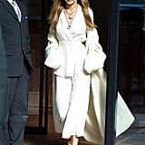 "Gigi Hadid embraced her Winter whites in a Zeynep Alcay ""kimono suit."" She wore her Stuart Weitzman evil eye mules (that she designed with the brand), a fuzzy Elisabeth Stray Pedersen cardigan, jewels by Toni + Chloë Goutal, and tinted Illesteva sunglasses."