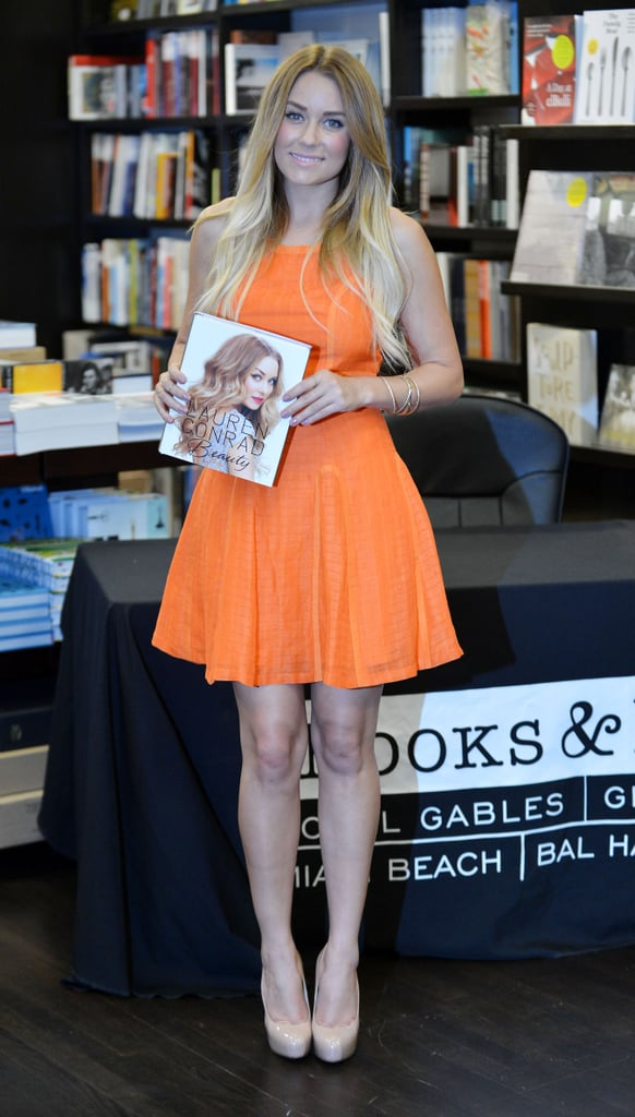 Lauren Conrad wore a bright orange dress to promote her books at a Miami bookstore.
