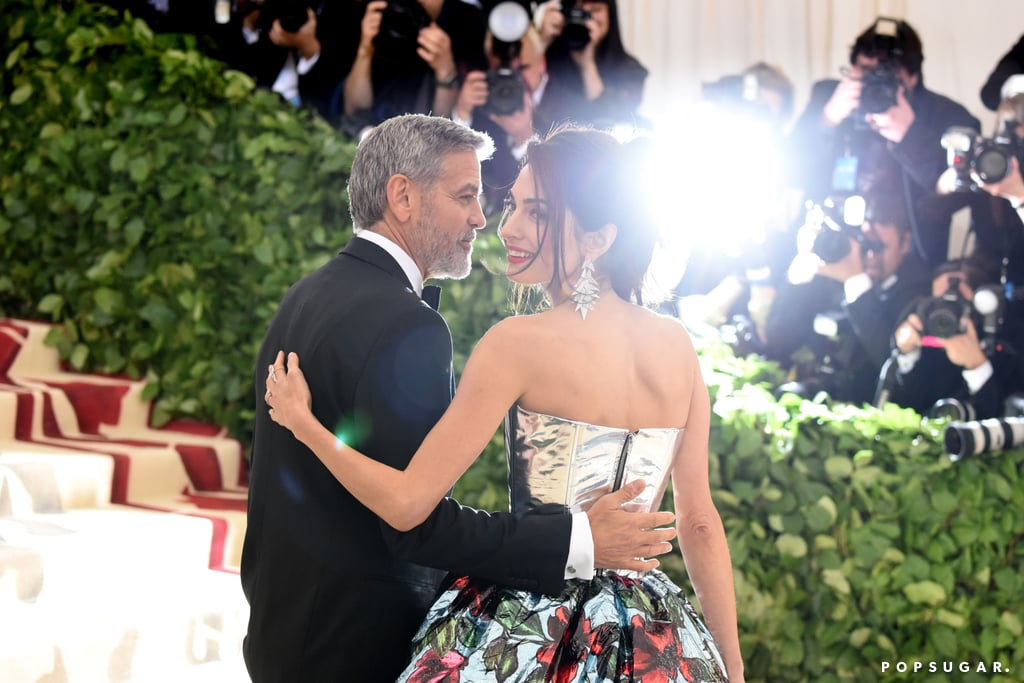 Amal and George Clooney enjoyed a fun night out as they attended the Met Gala on Monday in NYC. The couple, who are parents to twins Ella and Alexander, made one stylish pair as they walked the red carpet together outside of The Metropolitan Museum of Art in NYC. While George wore a black suit and bowtie, Amal, who is a cohost for this year's event, stunned in a floral bustier and train over sleek navy blue pants.  The appearance comes at an exciting time for the parents of two. While George recently turned 57 last weekend, their son and daughter are getting ready to celebrate their very first birthday on June 6. Even though they have kept their little ones out of the spotlight, they have given us a peak at their family life by gushing about them during interviews. We can't wait to see even more of the gorgeous couple when they attend the royal wedding later this month.       Related:                                                                                                           17 Times George and Amal Clooney Looked Madly in Love