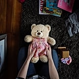 """Kristin holds her Molly Bear in Abby's nursery. Molly Bears is a nonprofit organization that creates weighted teddy bears, the approximate weight of the deceased infant, for families coping with infant loss."""