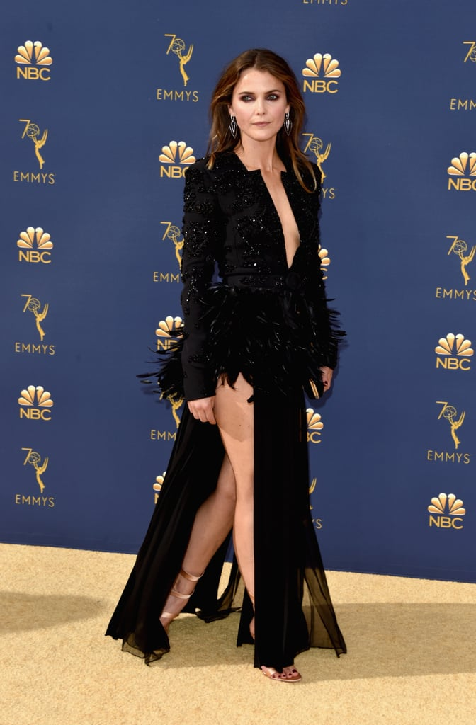 Keri Russell arrived at the Emmys on Sept. 17 dressed to impress and left us all with our jaws on the floor. The Americans actress walked the red carpet in a sexy couture Zuhair Murad peplum jacket with feathers and a pleated skirt that showed off a whole lot of leg. Her dramatic black top featured a plunging neckline and was cinched at the waist with a belt.  She finished off her dark and dangerous look with metallic heels, dangling earrings, and a matching black clutch. It's no wonder she had to forbid Matthew Rhys from proposing during the show. For wearing that outfit? We'd get down on one knee too.      Related:                                                                                                           The Emmys' Sexiest Dresses Were on Another Level of H-O-T