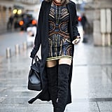Alessandra Ambrosio wearing a Versace Couture dress, a Baja East cardigan, Gianvito Rossi boots, a Versace bag, a choker by Shay Jewelry, and Linda Farrow sunglasses.