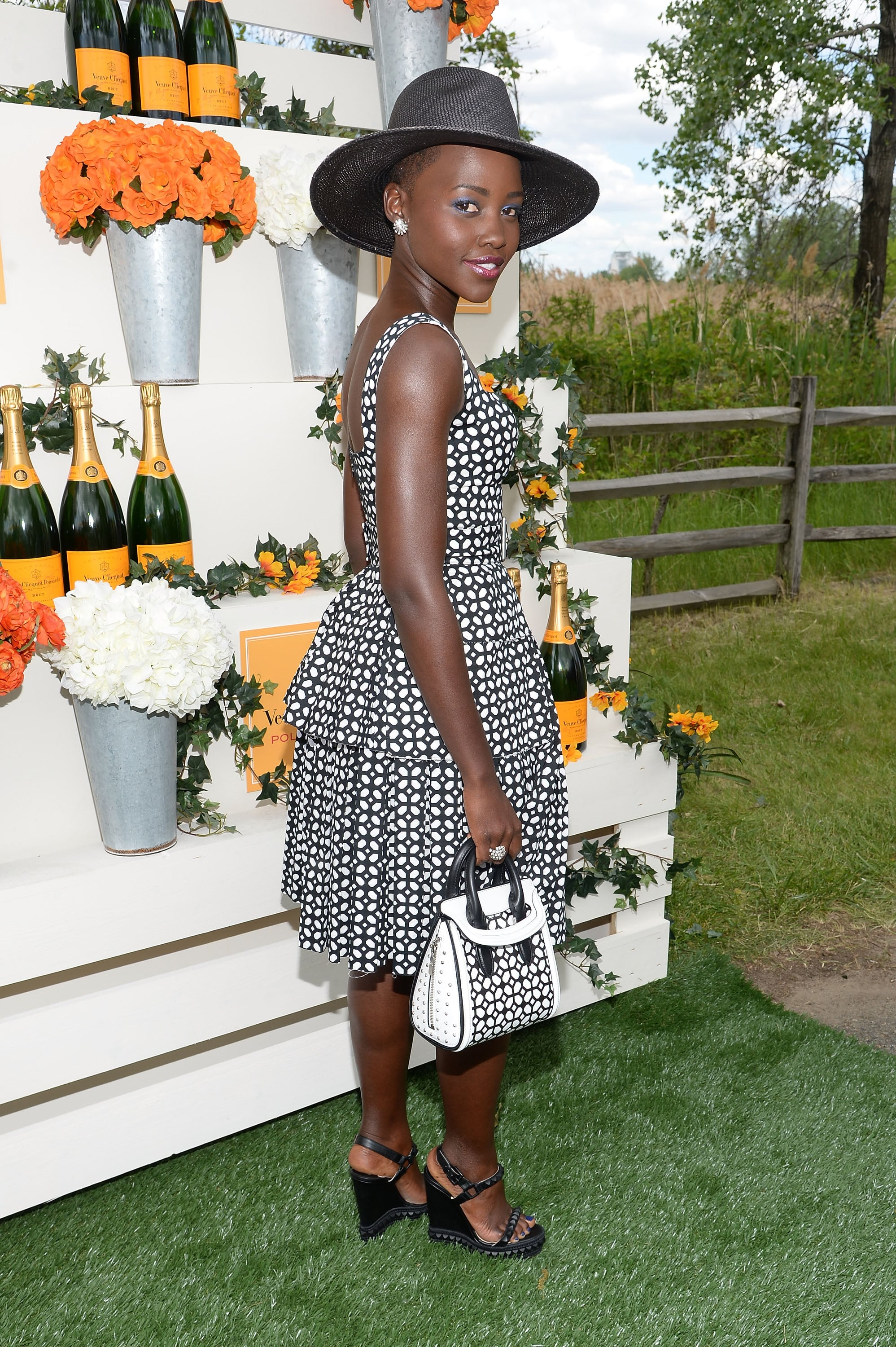 Lupita wore a patterned dress that matched her purse.