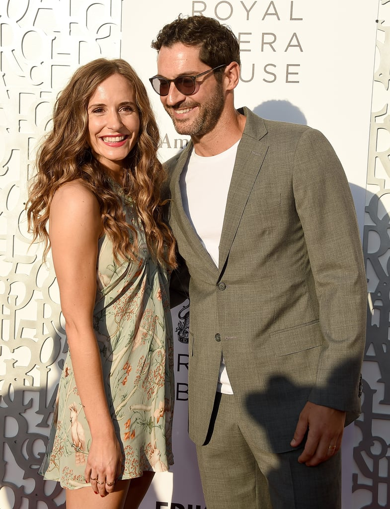 It's safe to say that Tom Ellis and Meaghan Oppenheimer have the look of love down pat. The 41-year-old Lucifer star and the 34-year-old screenwriter, who wed in June 2019 after four years of dating, have given us quite a few glimpses into their adorable relationship. Whether they're documenting their at-home hangouts or sharing a laugh on the red carpet, the pair sure knows how to make us swoon. And let's not forget about their sweet family moments with Tom's 15-year-old eldest child, Nora — whom he shares with ex-girlfriend Estelle Morgan — and his daughters Florence, 12, and Marnie, 8 — whom he shares with ex-wife Tamzin Outhwaite. Keep scrolling to revel in Tom and Meaghan's cutest snaps!      Related:                                                                                                           Lucifer Fans Are In For a Devilish Treat: Netflix Extended the Fifth Season to 16 Episodes