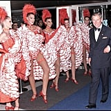 Prince Charles couldn't help but grin as he passed a group of dancers at the Moulin Rouge premiere in 2001.