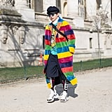 A Fashion Week guest rocked a long rainbow coat with dad sneakers.