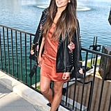Shay Mitchell attended the Kaleidoscope x Delta Air Lines event in a tangerine slip dress, Ash boots, and a rose-printed leather jacket from Revolve.