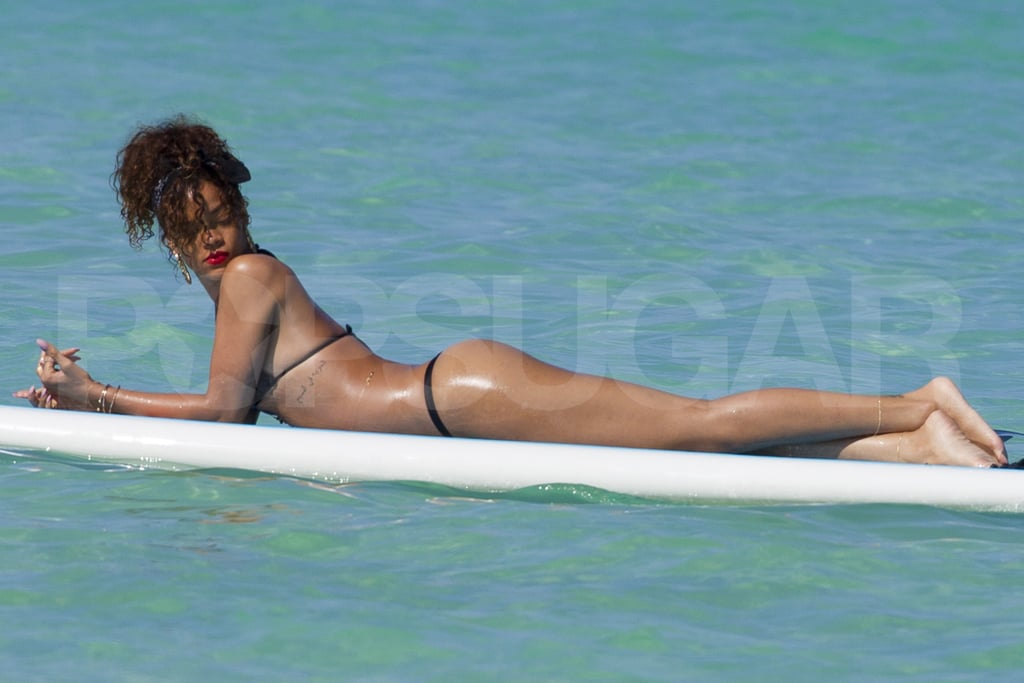 Rihanna lounged on a surfboard.
