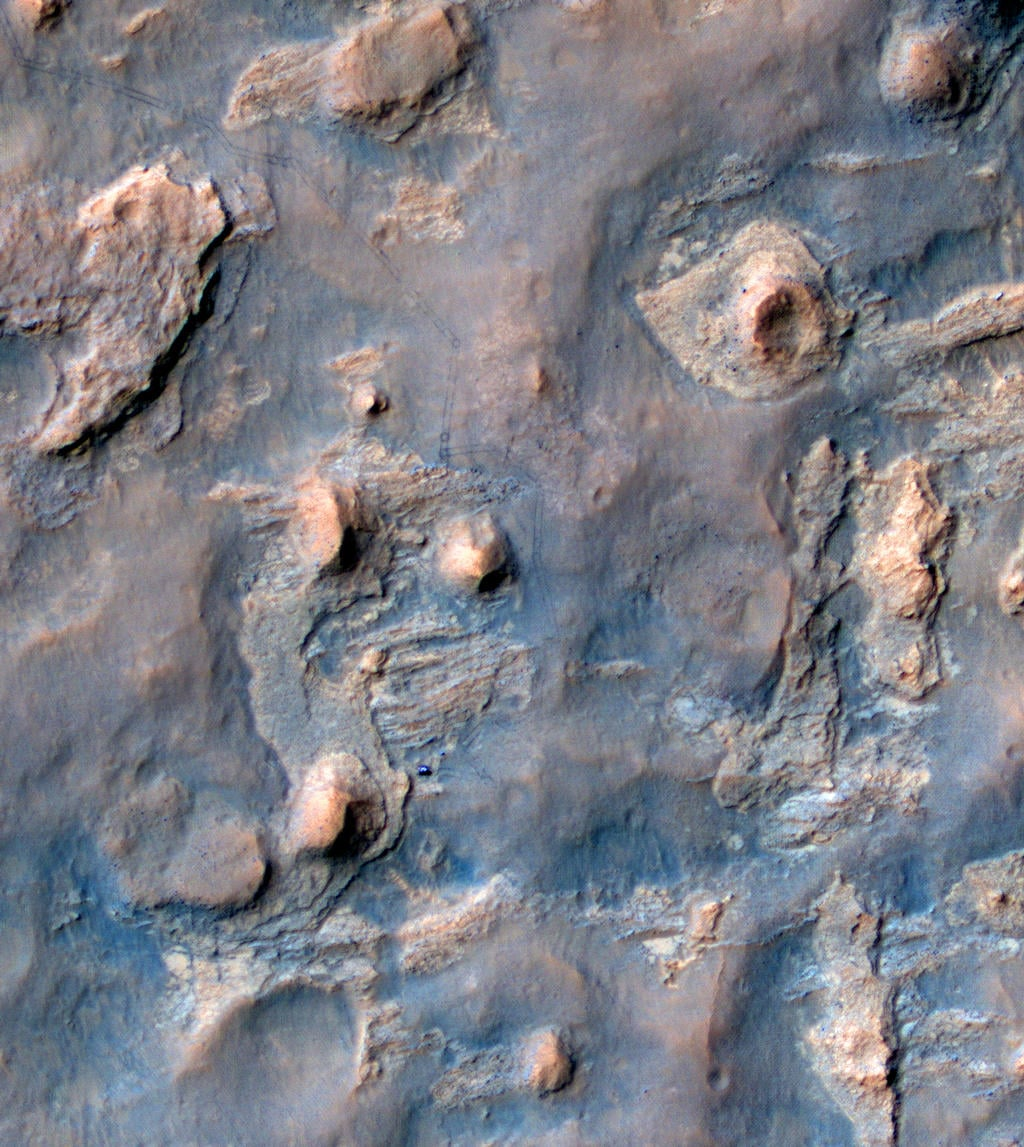 Here we see the Curiosity rover — the bright blue figure near the large hill in the lower left area — and its tracks in this view from orbit.  Source: NASA/JPL-Caltech/Univ. of Arizona