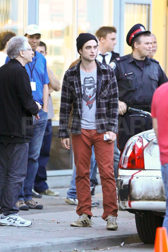 Robert Pattinson threw on his favorite red pants, a beanie, and a plaid shirt to rehearse scenes for Cosmopolis in Toronto this afternoon. It was a different look than the usual buttoned up suit that he's been sporting for the cameras when he gets into character. Rob's been filming in Canada all month, but he did take a break from work to travel to LA for the MTV Movie Awards. Rob met up with Kristen Stewart for the show, where they presented an exciting new clip from Breaking Dawn. The couple are back on opposite coasts, though since Kristen Stewart was spotted at yoga in LA earlier today.