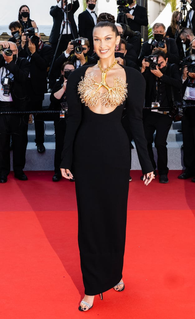 Bella Hadid only brought breathtaking looks for the Cannes Film Festival this year. From classic gowns to Clueless-inspired sets, her outfits are consistently chic. Each look is eye-catching in its own way, but her couture Schiaparelli pick at the Tre Piani premiere is truly her sexiest gown yet.  The sleek sleeved black dress needed no neckline. Instead, Bella wore a massive brass necklace in the shape of branched lungs adorned with rhinestones to cover her chest. The statement piece did all the talking, but the model managed to add to the look with glittering earrings and sophisticated heeled sandals by Giuseppe Zanotti. Get a glimpse of Bella's ensemble from all angles in the photos ahead.       Related:                                                                                                           Timothée Chalamet Is Just One of the Celebs Doing the Most at the Cannes Film Festival