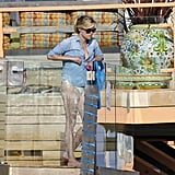 Reese Witherspoon throws on a denim cover up.