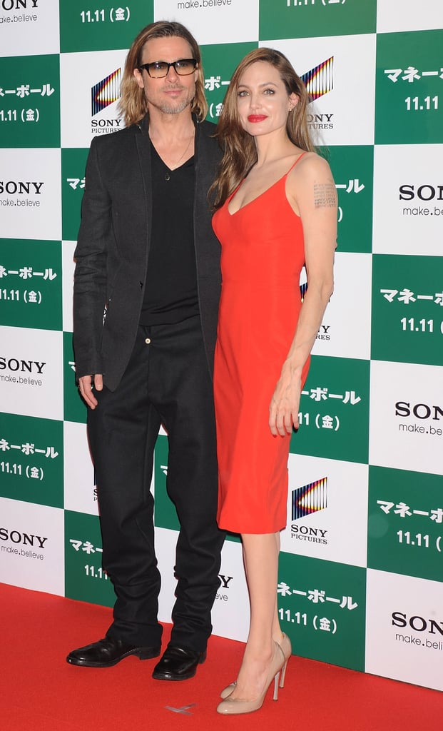 Brad Pitt was in premiere mode today for a screening of Moneyball during the Tokyo International Forum for film. Angelina was in a chic and simple, tight red dress to join Brad on the carpet, and the couple held hands before striking their poses for photographers. Brad was solo afterward, though, when he took the stage to address reporters before the screening and pose with some Japanese baseball players. Brad, Angelina, and their kids arrived in the country just yesterday following a Fall spent in Europe. The Jolie-Pitts moved from Malta to Scotland, England, and on to Hungary as Brad shot World War Z. Next up for Brad and Angelina will be her busy Winter promoting In the Land of Blood and Honey, and, perhaps, a jam-packed award season if either picks up nominations for their various film endeavors.