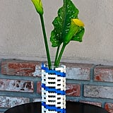 If you're tired of your simple glass vases, you can up the geek factor by building an arrangement of Legos around it. Instant color and quirk. See more Lego décor here. Source