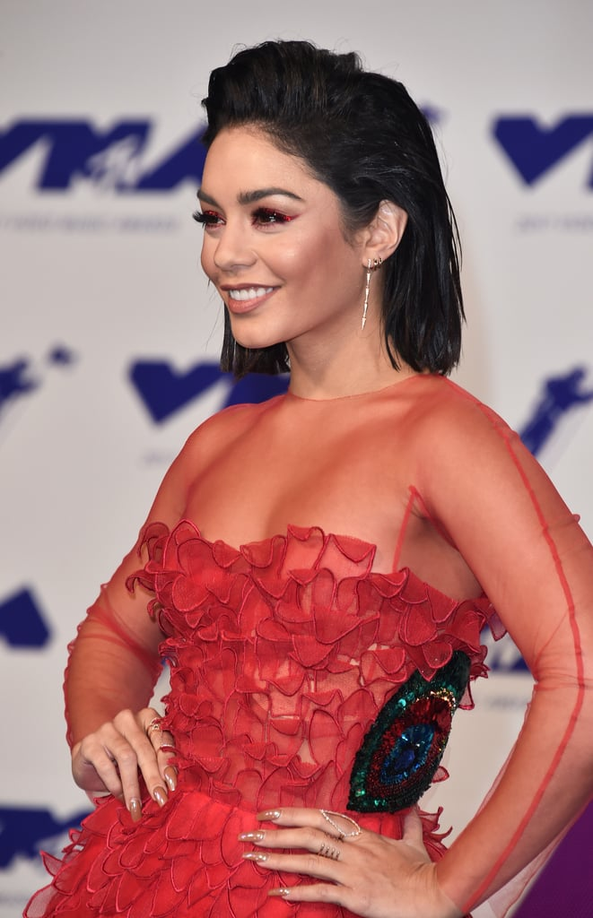 The 2017 MTV VMAs may have been lacking a red carpet that was actually red, but don't worry — Vanessa Hudgens brought plenty of the bold color when she arrived.  The actress was sporting a lovely red dress with a sheer panel that showed off her toned legs, but we really couldn't help but focus on her voluminous hair and glam makeup. Hairstylist Chad Wood started by applying John Frieda's Luxurious Volume Root Booster Blow-Dry Lotion on Vanessa's wet locks, which he then blow-dried and straightened. To achieve that polished, slightly wet look, Wood used John Frieda's Frizz Ease Secret Weapon Touch-Up Crème and locked in the look with some hairspray. We'll definitely be citing her as inspiration on those mornings when we actually just woke up late and didn't have time to blow-dry our hair before work! From far away, Vanessa's VMAs makeup looked pretty simple. But once we zoomed in, we saw that she was wearing quite an unexpected, statement-making eyeliner color: red! Makeup artist Allan Avendaño used Christian Louboutin's Oeil Vinyle Luminous Ink Liner in the Rouge Louboutin Vibrant Red hue, followed by actual red Swarovski crystals for that extrasparkly oomph. Anyone else getting holiday vibes? Avendaño finished off Vanessa's bold eye makeup by using false lashes from his collaboration with Artémes Lashes, which will make its debut soon. The actress kept the rest of her makeup relatively muted (including tan nail polish), opting for slightly bronzed cheeks and a nude lipstick, letting her fiery-winged liner do all the talkin'. We'll be the first to admit that we usually stick to our tried-and-true brown or black eyeliner, but Vanessa is certainly making us want to step outside our comfort zones and give this fiery hue a try!  Ahead, get an up-close look at Vanessa's slicked-back hair and red-hot makeup, and then check out the rest of our favorite beauty looks at the VMAs.