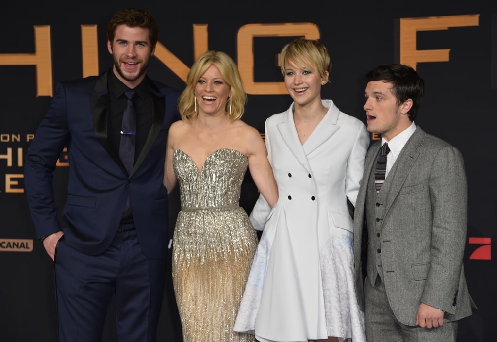 It looks like it's all fun and games once you're outside the arena. The cast of The Hunger Games: Catching Fire headed to Berlin on the latest stop in their promotional tour, and there were plenty of laughs to go around. Jennifer Lawrence had another winning look with her white coat dress from Dior, while Elizabeth Banks rocked a floor-length Elie Saab gown. The girls posed for pictures with Josh Hutcherson and Liam Hemsworth, and it seemed the group couldn't stop themselves from laughing with each other! We're not surprised to see more red carpet shenanigans from Jennifer, especially after her tickle fight with Josh at the world premiere in London on Monday.