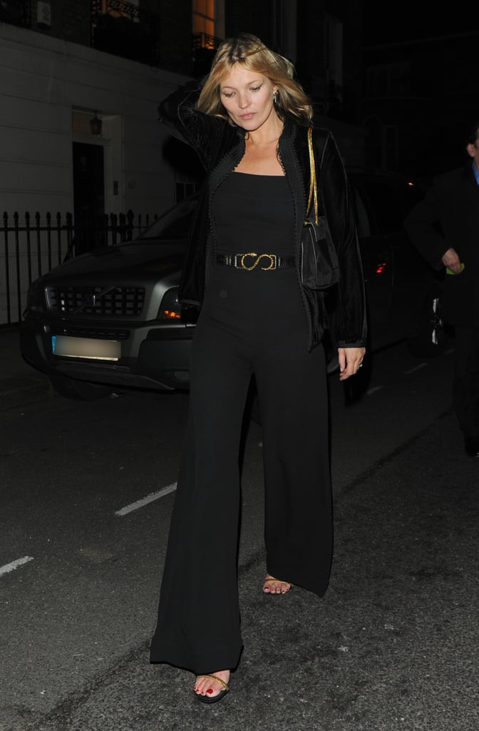 Kate Moss hit the streets in a black wide-leg jumpsuit, topped with a black velvet jacket, finished with gold sandals and a black bag with gold chain handles.