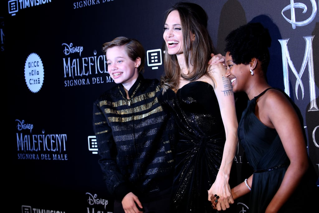 "The Maleficent: Mistress of Evil press tour is the gift that keeps on giving! On Monday, Angelina Jolie was joined by her kids, 14-year-old Zahara and 13-year-old Shiloh, at the European premiere of the film in Rome, Italy. The 44-year-old actress and philanthropist donned a strapless black dress for the affair and Zahara and Shiloh made sure to match their mom in colour-coordinated outfits. The brood appeared to have a case of the giggles, and they stole the show as they posed for pictures together.  Maleficent: Mistress of Evil hits theatres on Oct. 18, and Angelina has had her kids by her side as she promotes the film. The mom of six was joined by Zahara and Shiloh, as well as 15-year-old Pax and 11-year-old twins Vivienne and Knox, at the LA debut and 18-year-old Maddox even took a break from college to support her at the Japan premiere. See photos from the fun family outing ahead!      Related:                                                                                                           Angelina Jolie Gets Candid About Her Divorce From From Brad Pitt: ""I Had Lost Myself"""