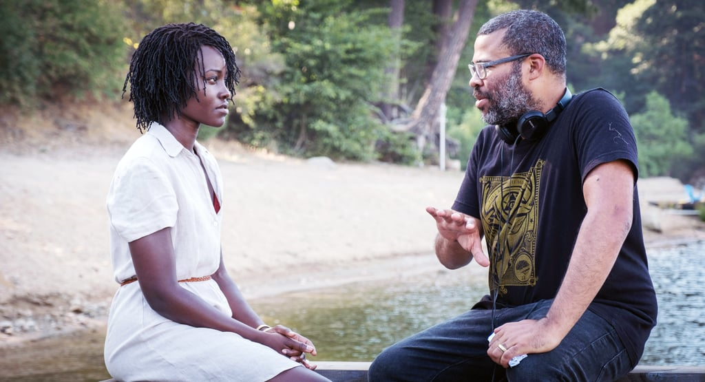"""If there's one thing we can all appreciate in Us, Jordan Peele's second feature film after his Oscar-winning Get Out, it's the view. Sure, it's mostly obscured by the murderous, jumpsuit-wearing doubles trying to annihilate Lupita Nyong'o and company, but that doesn't take away from the fact that the entire film takes place by the sunny beachside!  The film's synopsis explains that Adelaide (Nyong'o), Gabe (Winston Duke), and their kids, Zora and Jason (Shahadi Wright Joseph and Evan Alex) travel to Adelaide's beachside childhood home for an idyllic summer getaway in Northern California. Specifically, they travel to Santa Cruz where they """"relax"""" near the amusement park, Santa Cruz Beach Boardwalk, which Adelaide also visits with her parents when she's a young girl (played by Madison Curry). Peele's filming crew was seen with cast members in Santa Cruz back in September 2018, where most of the exterior shots for the movie were filmed. Aside from the days spent in the Santa Cruz, most of the film was shot in Los Angeles. The Wilson's family holiday house is located in Pasadena, with the lake scenes being shot at Lake Gregory. Check out some behind-the-scenes photos of Peele and the cast filming ahead and, if you're ever in Santa Cruz or Los Angeles, I would keep your eyes peeled (get it?) for any red jumpsuits. You never know who's lurking in the shadows . . .      Related:                                                                                                           Watch Lupita Nyong'o and the Cast of Us Rap to a Spooky Beat, and Just TRY Not to Nod Along"""