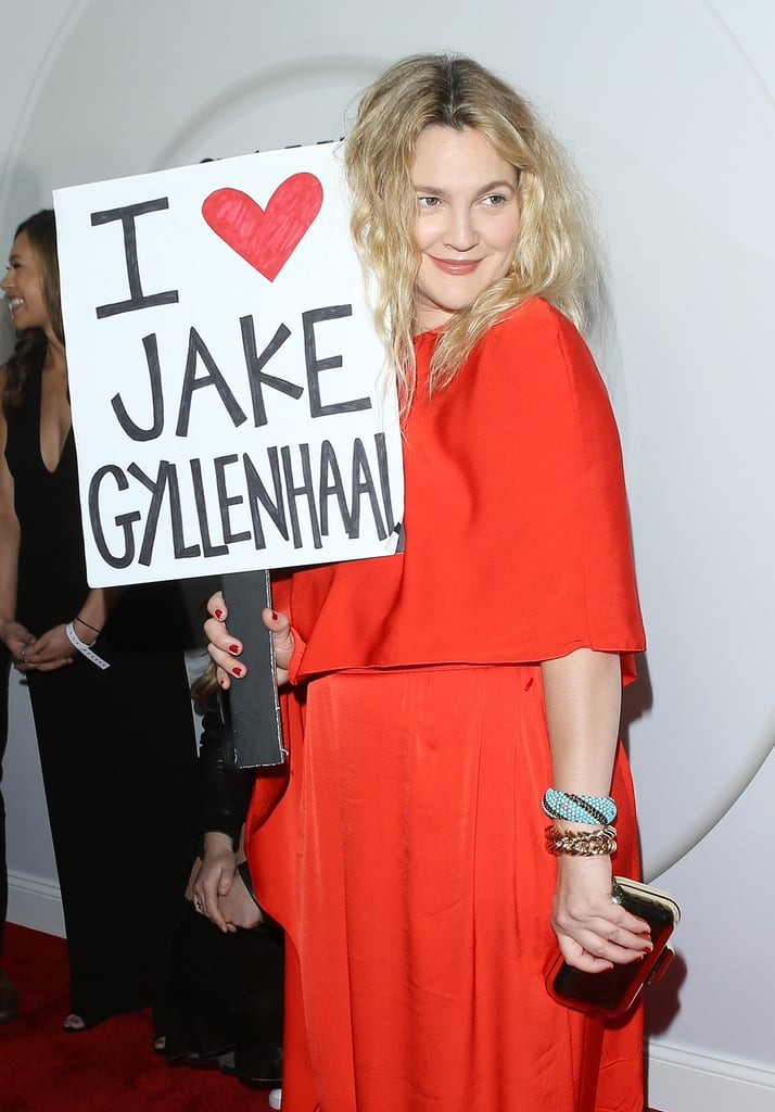 "Drew Barrymore wants Jake Gyllenhaal to know that he is indeed loved. The actress was recently forced to rank her previous costars in a cruel game on James Corden's The Late Late Show. After being put in a tough position, Drew ranked her Donnie Darko costar lower than Hugh Grant and Adam Sandler. Now, Drew is apologizing to Jake in the most public way possible.  At the premiere for the second season of Santa Clarita Diet, Drew brought along a little accessory: a sign that read ""I love Jake Gyllenhaal."" The actress walked the red carpet with the poster and posed for pictures to make her statement clear. See pictures of the hilarious stunt ahead."
