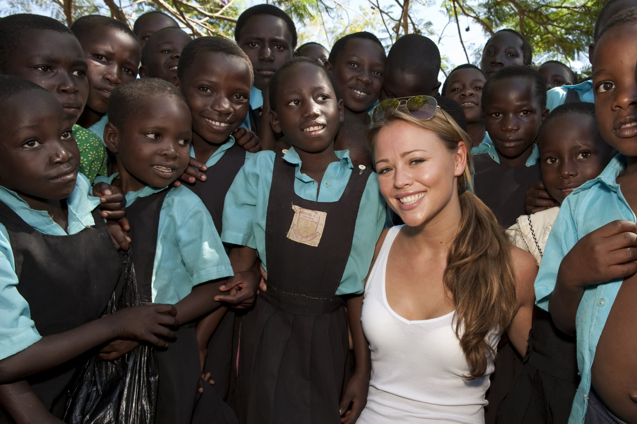 HOIMA, UGANDA - NOVEMBER 29: Kimberley Walsh poses with school local children as she visits a School where she is helping to hand out moquito nets on November 29, 2009 in Hoima, Uganda. Five of the nine celebrity Kilimanjaro climbers, Gary Barlow, Fearne Cotton, Ben Shepherd, Chris Moyles and Kimberley Walsh, saw all their hard work climbing the mighty Mount Kilimanjaro pay off as they witnessed for themselves how some of the money raised is being spent to help to fight malaria, Africa's biggest killer. The team are revisiting Africa to see how the money raised over Red Nose Day is being spent, as well as helping to hand out malaria nets. You can see how the team got on by watching BBC One 6.30pm Sunday 27th December.  (Photo by Des Willie/Comic Relief via Getty Images)