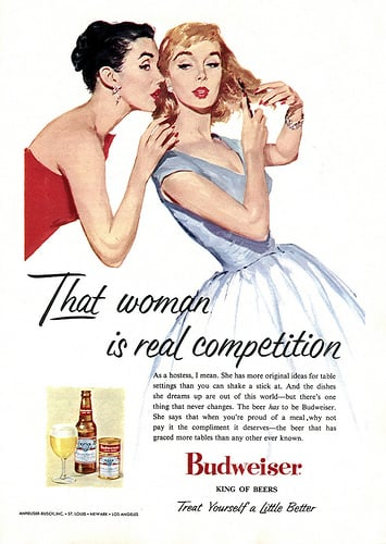 """This 1956 ad hopes to convince housewives that Budweiser will help them win the competition for best hostess ever. The copy reads, """"The beer has to be Budweiser. She says that when you're proud of a meal, why not pay it the compliment it deserves — the beer that has graced more tables than any other ever known."""""""