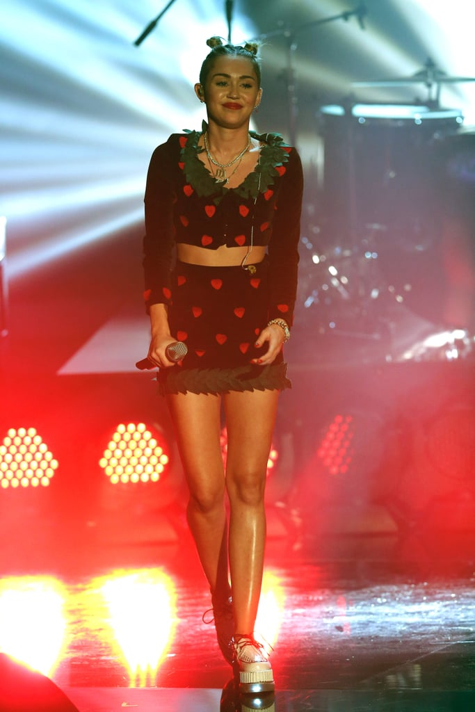 Baring her toned abs in a festive cropped jacket and miniskirt during a performance in Germany in November 2013.