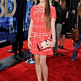 Her red Louis Vuitton shift dress, patent leather loafer pumps, and amazing Jimmy Choo face print clutch give us a lot to admire.