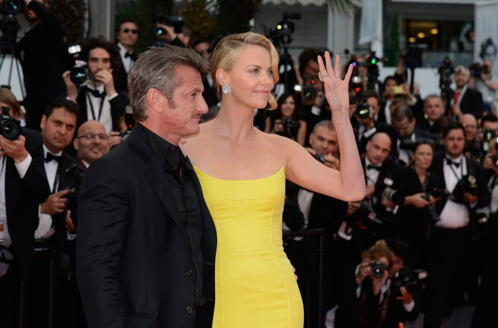 Charlize Theron stood out on the Cannes red carpet in a gorgeous yellow Dior gown for the Thursday premiere of Mad Max: Fury Road. The actress posed with her costars and also had boyfriend Sean Penn by her side. The couple walked the carpet arm in arm and held hands as they made their way up the stairs. While Sean and Charlize had more than a few picture-perfect moments, it was the rock on her ring finger that really turned heads. Charlize showed off the massive teardrop diamond by putting her left hand on her hip and throwing her arm over Sean's shoulder, perhaps trying to tell us something? The duo have been dating for more than a year and reportedly got engaged over the holidays, and though neither party has spoken out about their relationship status, Charlize did recently gush about Sean being the love of her life. So what do you think? Could that rock be Charlize's engagement ring?