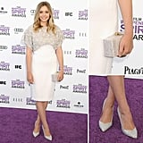 Keeping it sweet and ladylike on the purple carpet, Elizabeth Olsen donned a white knee-length Antonio Berardi sheath with gray floral beaded embellishments on the top half.  To accessorize, she chose a slick Edie Parker boxy clutch and crystal-encrusted pointy-toe pumps.