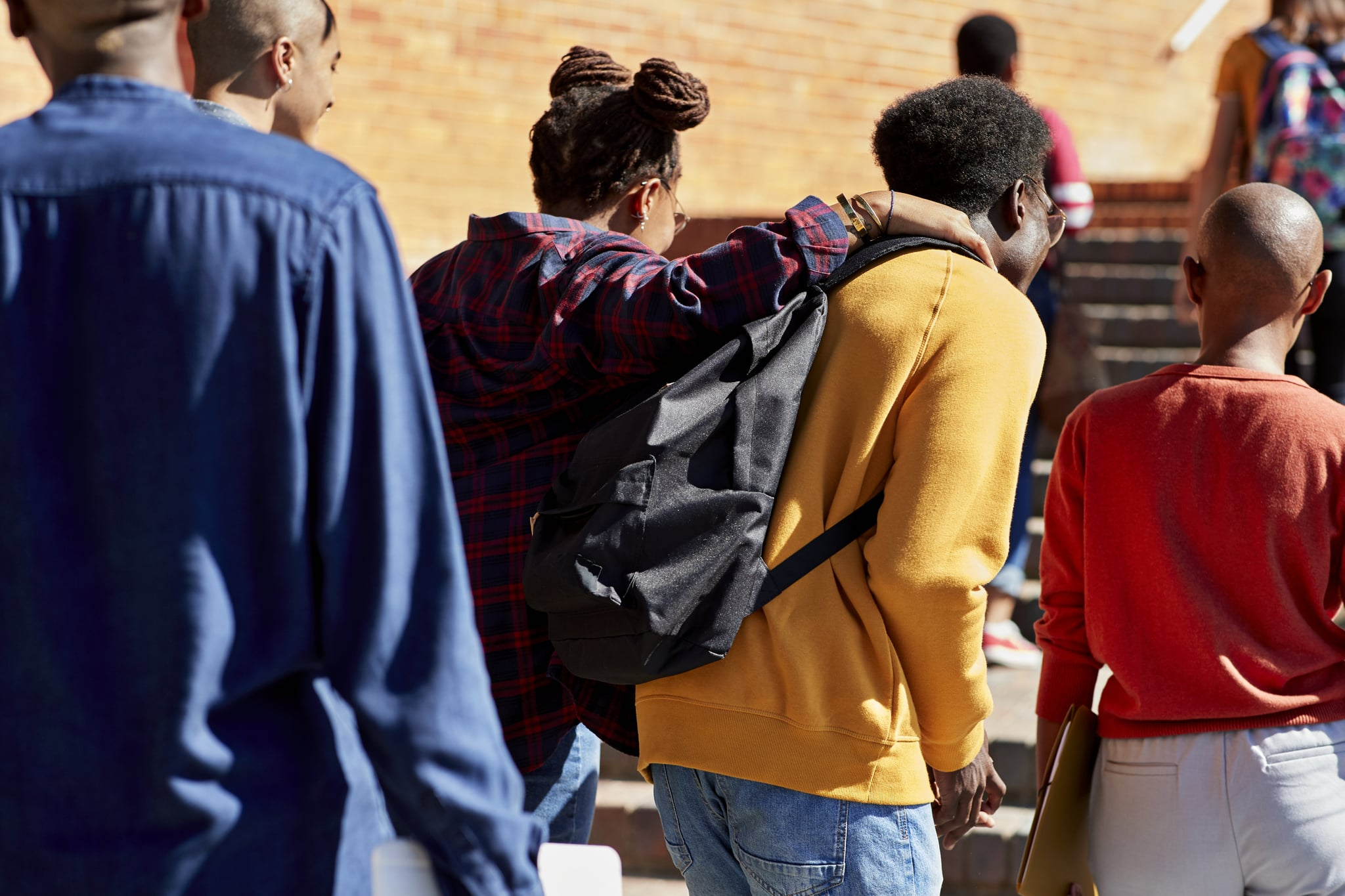 Rear view of man and woman walking with hand on shoulder with friends at university campus during sunny day