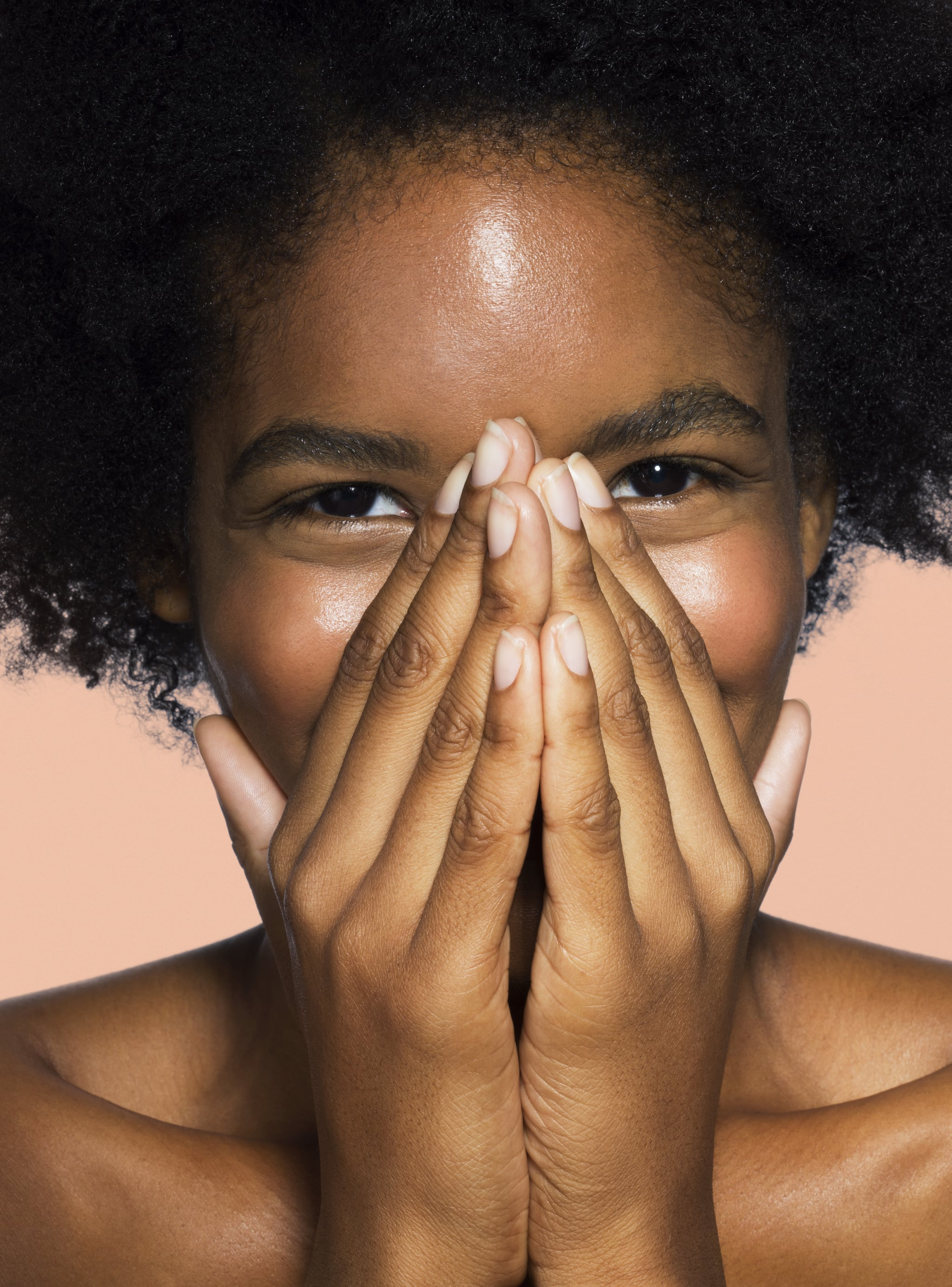 Young mixed-race female covering nose and mouth with hands with pink background