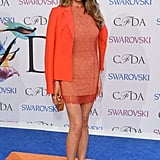 Chrissy Teigen wore an orange Rachel Roy ensemble.
