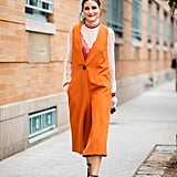While running around NYC, Olivia was a bright spot in an orange vest and emerald pumps.