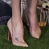 Charlize completed her look with nude pointy-toe Christian Louboutin pumps — check out her cute flower tattoo!