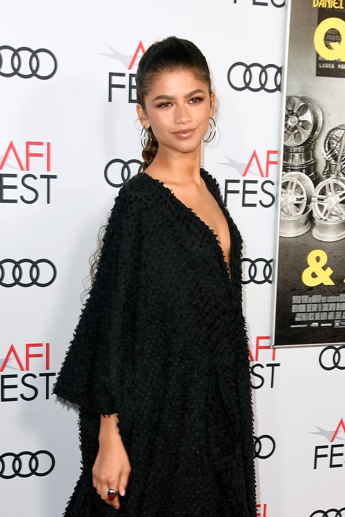 Zendaya is here to offer a lesson in dressing chic without sacrificing comfort. The actress recently attended the Queen & Slim premiere at the AFI Fest on Thursday wearing a textured caftan by Imane Ayissi. As a fun added detail, the oversize dress also comes with matching boots in the same fuzzy material from the Cameroonian designer's footwear collaboration with Goya Paris.  To complete the look, Zendaya's stylist, Law Roach, added a pair of spiral Kendra Scott hoop earrings. Also in attendance was Rihanna, who wore a similarly comfortable outfit consisting of a vintage John Galliano robe, which she paired with strappy stiletto sandals. Get Winter wardrobe inspiration and check out Zendaya's outfit ahead.