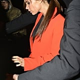 Victoria Beckham wore an orange jacket and skirt in London.