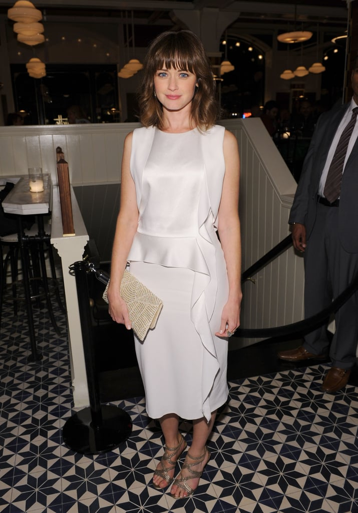 Alexis Bledel was entirely feminine in a white ruffled dress at the CAA Upfronts Party in NYC. Glittery gold sandals and a beaded clutch were the perfect add-ons to her polished style.
