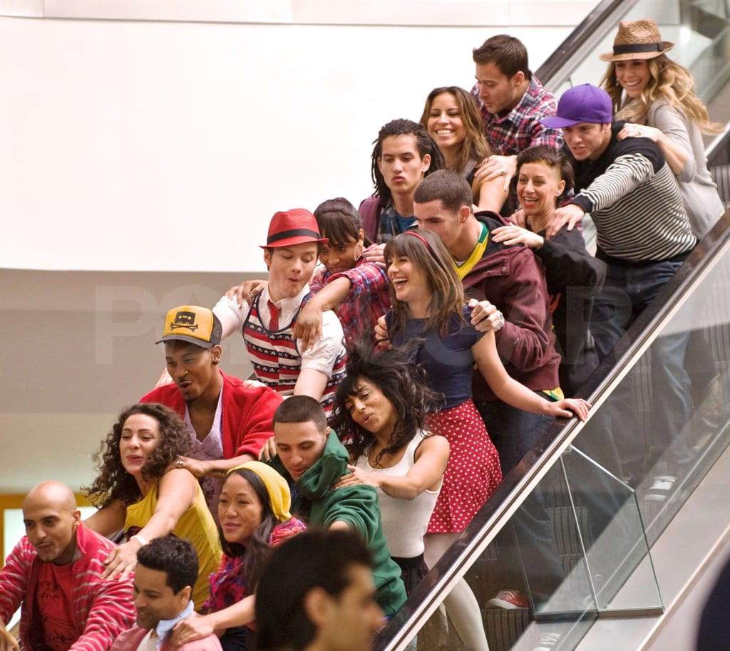 "Lea Michele, Chris Colfer, and Mark Salling hit the mall yesterday, but the Glee stars weren't engaging in any retail therapy. Instead, they were shooting the latest episode of their hit show and belting out a tune on their way down an escalator. It's been a hectic month of taping for the castmates as producers consider lengthening the upcoming ""Born This Way"" episode to 90 minutes instead of the usual 60. Many of the series' actors are still busy pursuing other projects despite the long hours. Mark and Chord Overstreet are two of the newest spokesmodels for OP, and Lea Michele recently spent time in NYC filming her big-screen role in New Year's Eve."